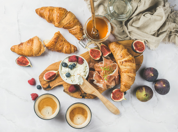 Breakfast with croissants, ricotta, coffee and berries over marble background