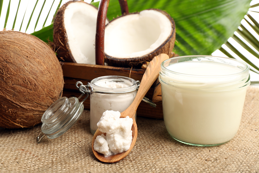 Coconut with jars of coconut oil and  milk on sackcloth on natur